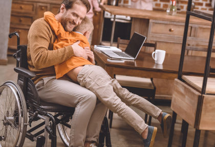 man in wheelchair with child